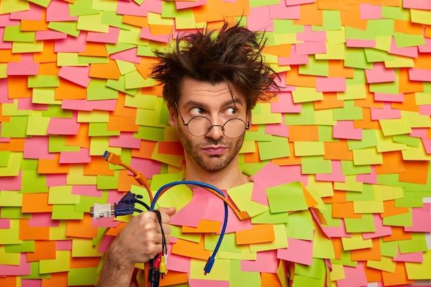 Ernstige bedachtzame man houdt een heleboel kleurrijke kabels vast, gaat de computer repareren, heeft een rommelig kapsel, kijkt door een optische bril, poseert tegen de muur met stickers. technologie, techniek