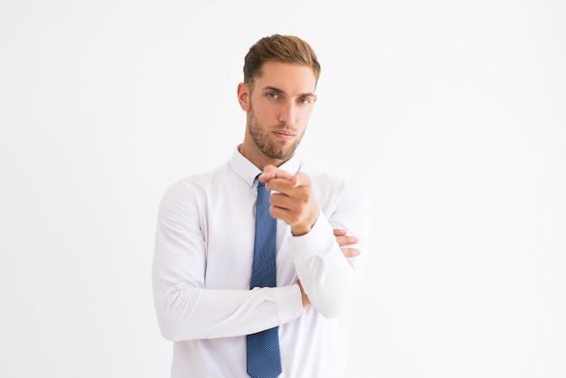 Ernstige bedrijfsleider die op u richt en camera bekijkt