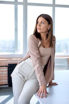 Ernstige bedrijfsleider executive poseren in kantoor zittend op bureau, alleen na vergadering