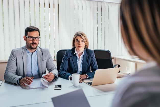 Ernstige bedrijfsmanagers die met een cliënt of een baankandidaat spreken.