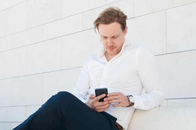 Ernstige bedrijfsmens die smartphone op bank in openlucht gebruiken