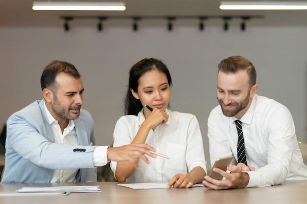 Ernstige bedrijfsmensen die en smartphone werken bij bureau gebruiken