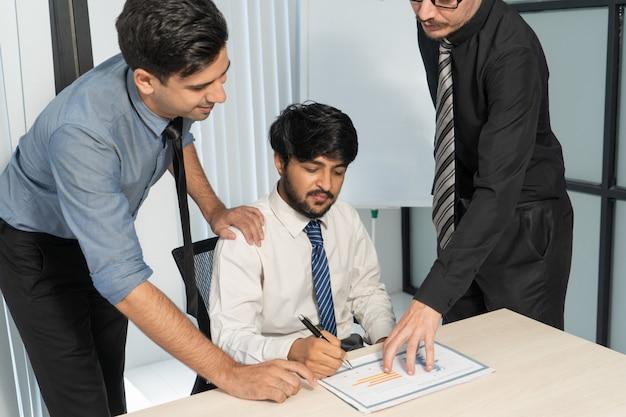 Ernstige bedrijfsmensen die inkomensgrafiek analyseren. commercieel team dat investeringsplan bespreekt.
