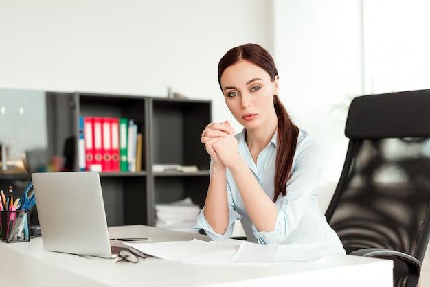 Ernstige bedrijfsvrouw die in het bureau bij het bureau met laptop werkt