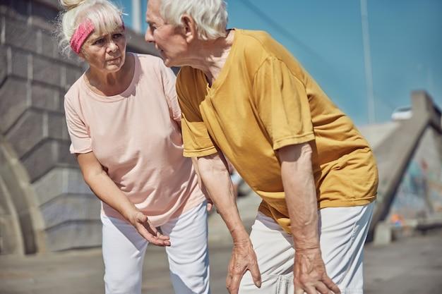 Ernstige bejaarde blanke vrouw die naar haar grijsharige echtgenoot staart die zijn knieën met beide handen aanraakt