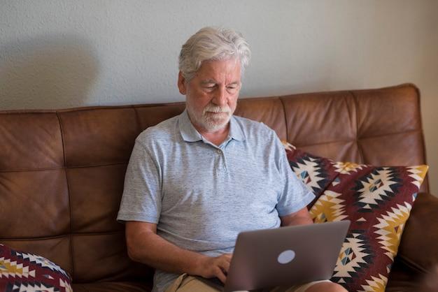Ernstige bejaarde ontevreden grijsharige man zit op de bank en kijkt naar het apparaatscherm dat werkt