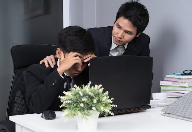 Ernstige benadrukt twee zakenman met behulp van laptop aan het werk project