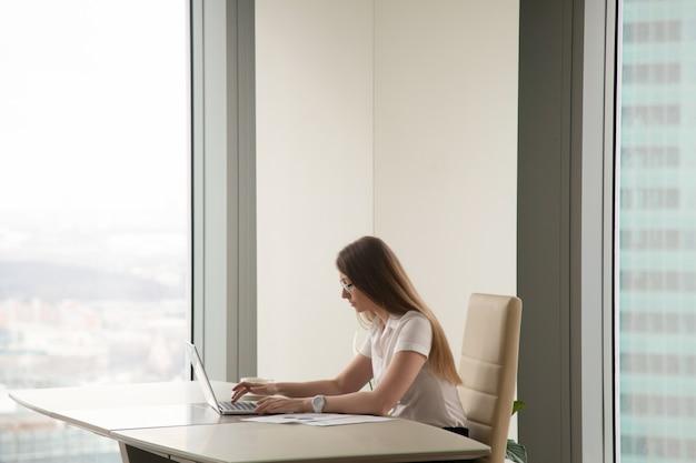 Ernstige bezige vrouw die aan laptop in bureaubinnenland werkt, copyspace