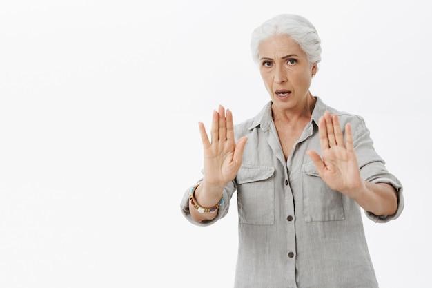 Ernstige bezorgde grootmoeder die haar handen opstak in een stopgebaar, zeg dat ze moet kalmeren