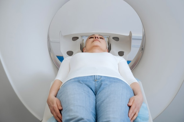 Ernstige bezorgde ongelukkige patiënt die op de onderzoekstafel ligt en wacht op het begin van de diagnostiek tijdens een bezoek aan een ziekenhuis