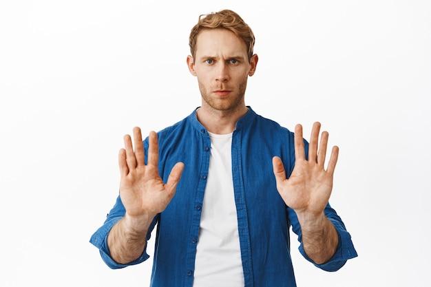 Ernstige bezorgde roodharige man toont blok stop gebaar, zeg nee, weiger of weiger aanbod, staande tegen een witte muur