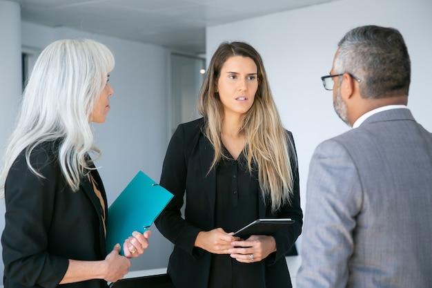 Ernstige bezorgde vrouwelijke manager met tabletrapportage aan de ceo van het bedrijf. gemiddeld schot. zakelijke communicatie concept
