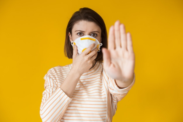 Ernstige blanke dame die het stopbord toont terwijl ze een masker met filter op een gele muur draagt
