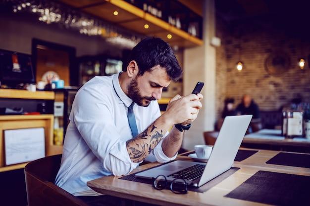 Ernstige blanke getatoeëerde bebaarde zakenman in overhemd en stropdas zitten in café, slimme telefoon te houden en te denken. op tafel voor hem staat een laptop.