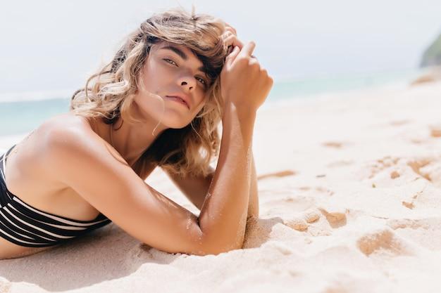 Ernstige blanke vrouw liggend op het strand en kijken. buitenfoto van vrolijk gelooid vrouwelijk model in zwarte zwembroek.