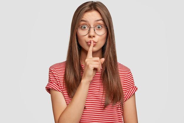 Ernstige blanke vrouw met donker haar verbergt fout van baas, toont stil gebaar