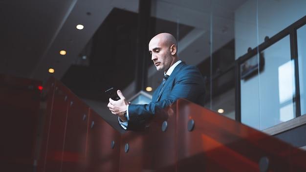 Ernstige blanke zakenman houdt online bijeenkomst via telefoon. onderaanzicht van man maakt gebruik van mobiele telefoon