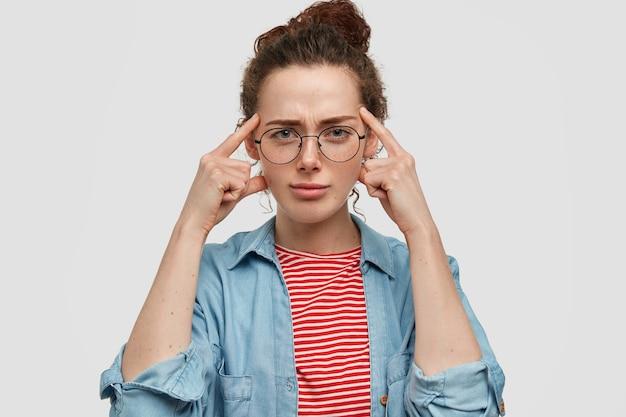 Ernstige blauwogige mooie jonge vrouw met bril, houdt vingers op slapen, heeft een doordachte, slimme uitdrukking, probeert zich iets in gedachten te herinneren, heeft een huid met sproeten en een specifiek uiterlijk