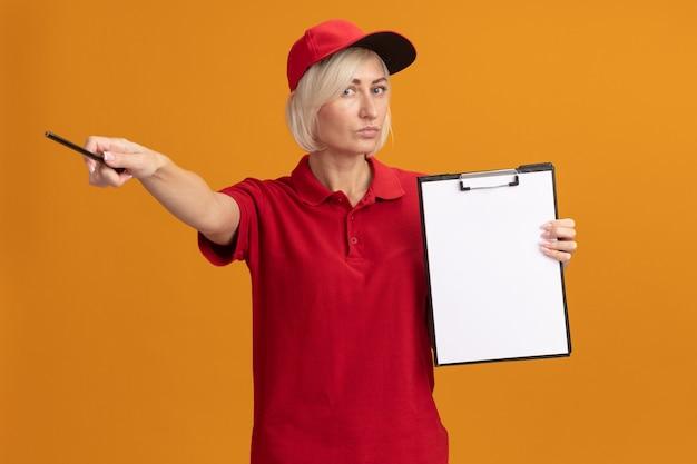 Ernstige blonde bezorger van middelbare leeftijd in rood uniform en pet met klembord kijkend naar de voorkant wijzend naar de zijkant met potlood geïsoleerd op oranje muur