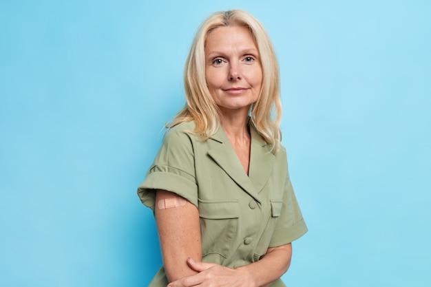 Ernstige blonde europese vrouw toont gevaccineerde arm nadat vaccininjectie dess poses tegen blauwe muur draagt