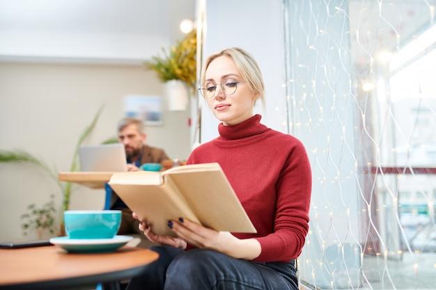 Ernstige blonde mooie vrouw die in toevallige sweater en jeans boek lezen terwijl het doorbrengen van tijd in koffie door kop van koffie