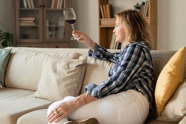 Ernstige blonde rijpe vrouw in vrijetijdskleding met glas rode wijn en kijken naar de drank zittend op de bank in de thuisomgeving