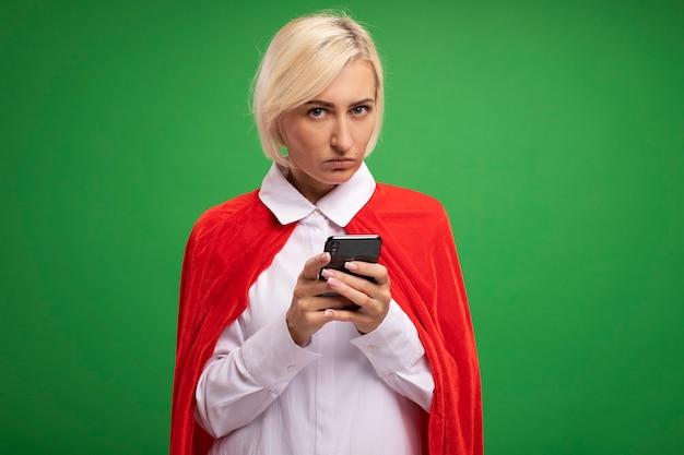 Ernstige blonde superheld vrouw van middelbare leeftijd in rode cape met mobiele telefoon