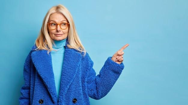 Ernstige blonde veertig jaar oude blanke vrouw heeft nieuwsgierige uitdrukking en geeft weg op lege ruimte draagt optische bril stijlvolle bontjas.