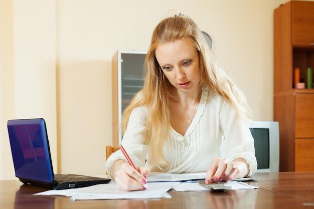 Ernstige blonde vrouw vult documenten in