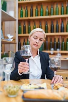 Ernstige blonde vrouwelijke professionele sommelier kijken naar rode wijn in wijnglas zittend door werkplek in kelder