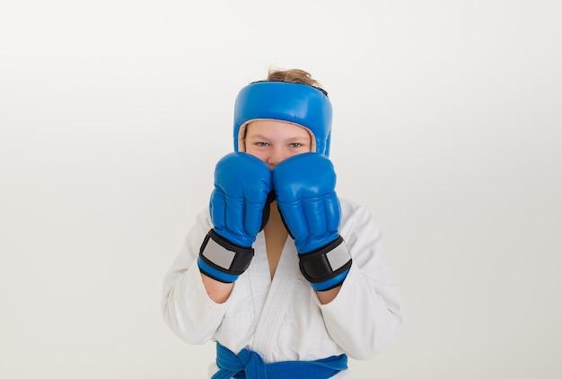 Ernstige bokserjongen die een helm en handschoenen draagt, staat in een pose op een witte muur