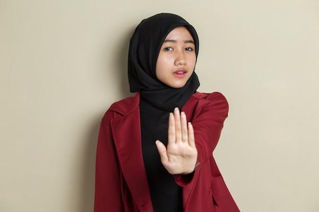 Ernstige boos aziatische moslimvrouw die het gebaar van de stophand toont