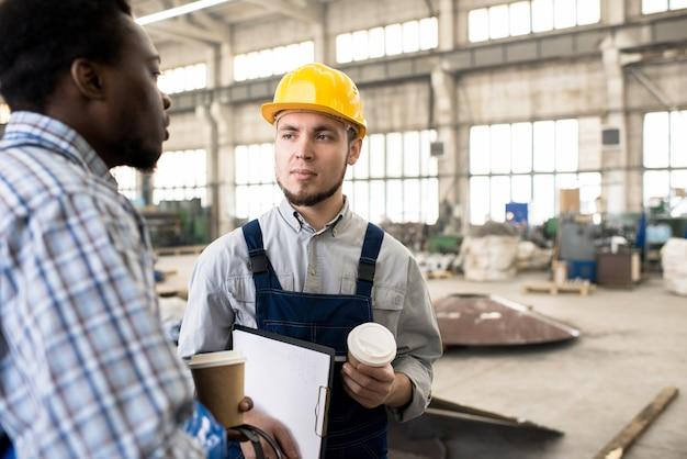 Ernstige bouwcollega's die koffiepauze maken