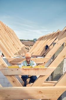 Ernstige bouwer in een veiligheidshelm knielend bij een houten bar en een waterpasinstrument gebruikend