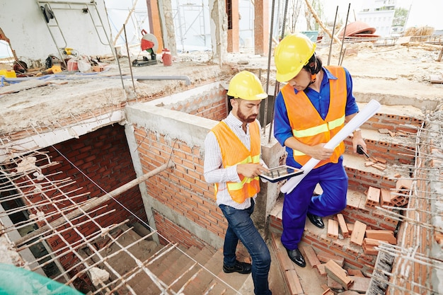 Ernstige bouwvakkers lopen de bakstenen trap op en bespreken het werkplan voor vandaag