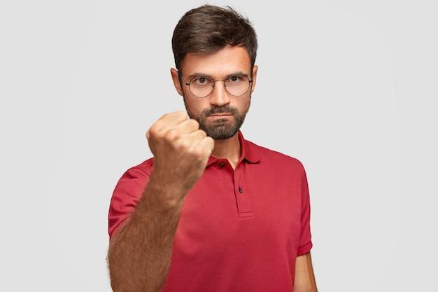 Ernstige boze man toont vuist, klaar voor strijd of uitdaging, heeft een strenge uitdrukking, draagt een casual rood t-shirt, poseert tegen een witte muur. agressieve jongeman gebaren binnen. lichaamstaal concept