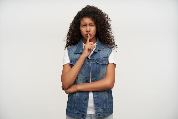 Ernstige bruinogige jonge brunette gekrulde vrouw met donkere huid houdt de wijsvinger op haar lippen en fronst ernstig wenkbrauwen, vraagt om stilte te houden terwijl ze poseren op wit