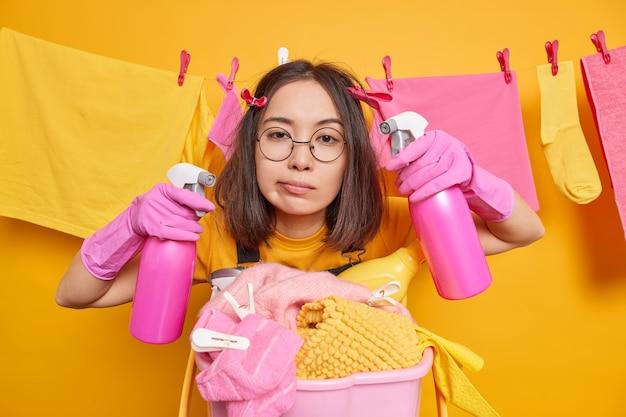 Ernstige brunette aziatische vrouw heeft vermoeide uitdrukking en houdt twee spuitflessen tegen waslijn