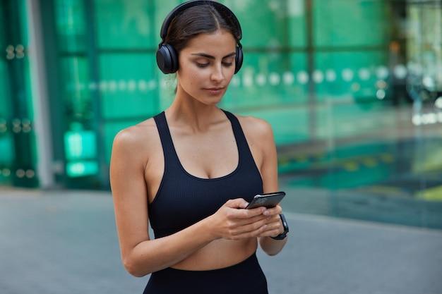 Ernstige brunette sportvrouw gekleed in bijgesneden top typen sms-berichten luistert audiotrack in koptelefoon heeft fitnesstraining wazig