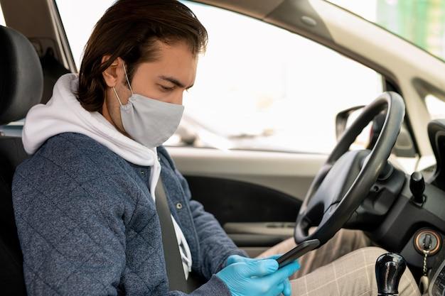 Ernstige brunette taxichauffeur in doek masker zit op het stuur en het controleren van kaartpunt op smartphone