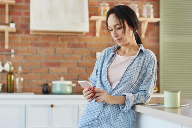 Ernstige brunette vrouw berichten online, maakt gebruik van gratis internetverbinding, draagt casual shirt,