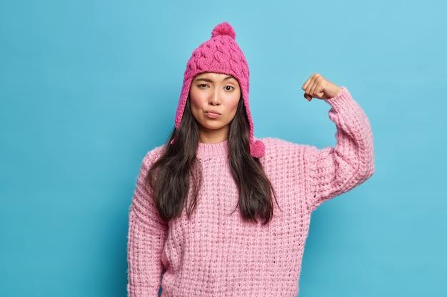 Ernstige brunette vrouw heft arm op en toont spieren zelfverzekerd en vol kracht draagt gebreide trui roze hoed voelt sterk gezond geïsoleerd over blauwe muur