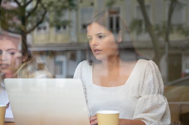 Ernstige brunette vrouw zittend aan tafel in de buurt van blonde collega