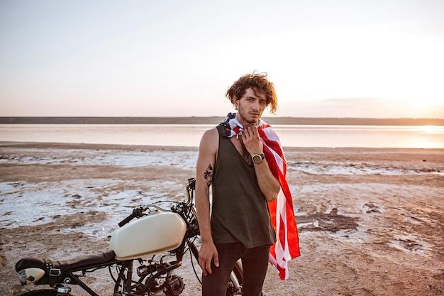 Ernstige brutale man met amerikaanse vlagkaap en gouden helm staande in de buurt van een motorfiets in de woestijn