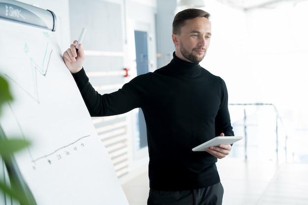 Ernstige business trainer grafiek uit te leggen