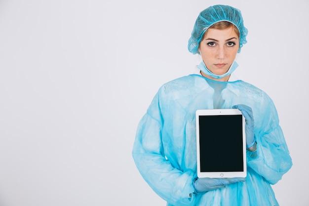 Ernstige chirurg met tablet en kopie ruimte