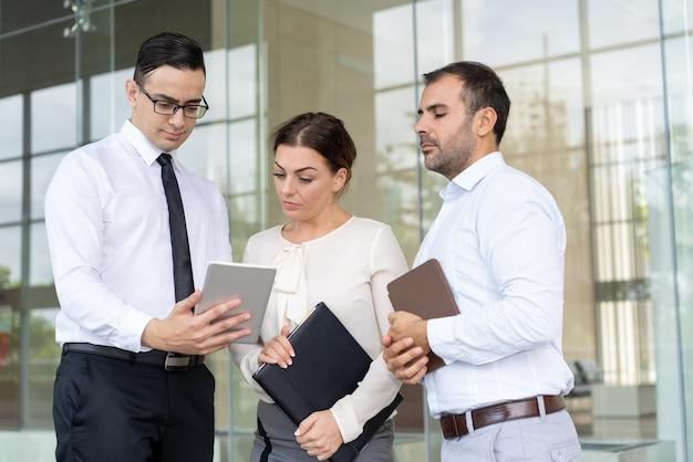 Ernstige collega's die e-mail met bedrijfsgegevens lezen