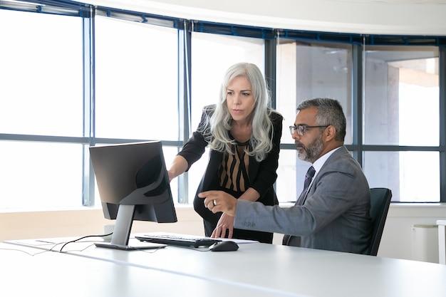Ernstige collega's kijken en bespreken inhoud op computermonitor, wijzend op het beeldscherm en praten zittend in de vergaderruimte met panoramisch raam. zakelijke communicatie concept