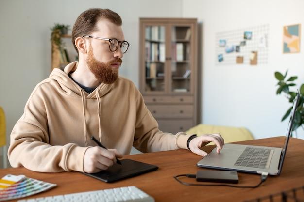 Ernstige creatieve jongeman in hoodie bezig met ontwerpproject met tekenblok in kantoor aan huis
