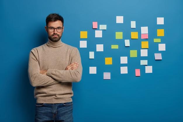 Ernstige creatieve man draagt een bril, bruine trui en spijkerbroek, staat met gekruiste armen tegen blauwe muur